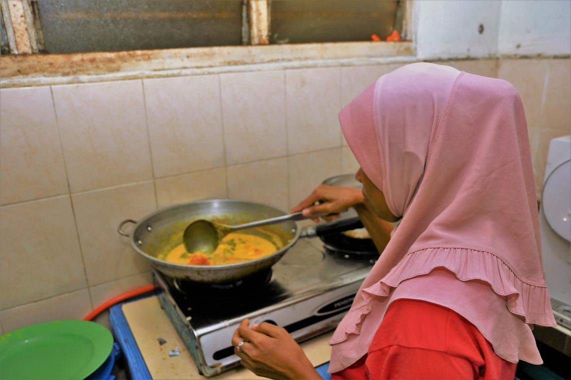 Lady in headscarf cooking