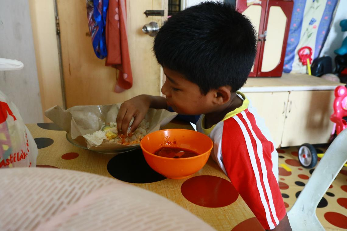 Boy eats rice and curry