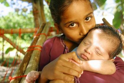 A young girl hugs her baby sibling on an island in Maldives.