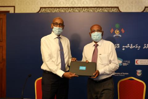 Minister of Health and UNICEF Rep holds laptop for a photo