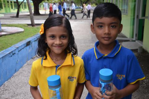 Two 6-year-old students smile after receiving their water bottles at a launch event on Fuvahmulah Island.