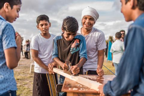 young boys using carpentry tools at a children's event stall
