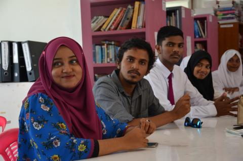 Four students sit at a table in a classroom in Addu City.