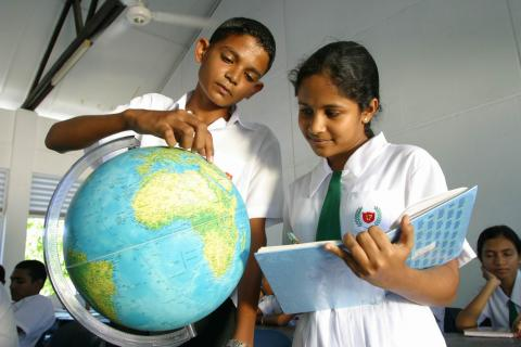 Two students look at a globe in a Maldivian classroom.