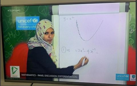 A female teacher conducting a mathematics lesson on a televised learning program