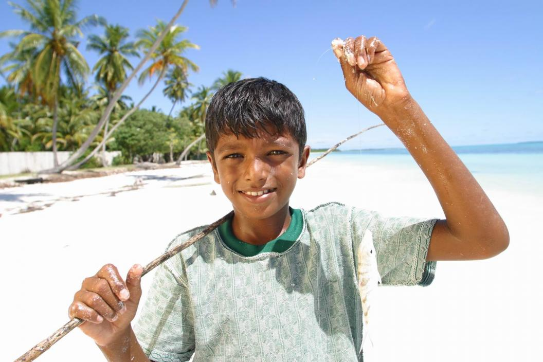A boy smiles as he holds up the fish he caught on a beach.