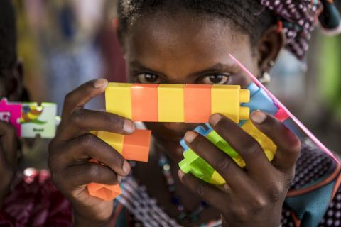 A girl hides behind a puzzle provided in a UNICEF kit in the informal settlement in Banguétaba. Psychosocial sessions for children were set up to cater to the needs of children who have fled the increasing violence in central Mali. Banguétaba, on the edge of Sévaré town, in the Mopti region, in central Mali, April 2019.
