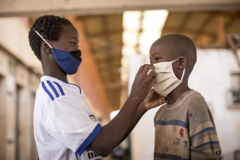 Samba*, 13 (left), helps a friend put on a face mask at a temporary shelter opened in Bamako by UNICEF and its partner Samusocial to support children living in the street during the COVID-19 pandemic.