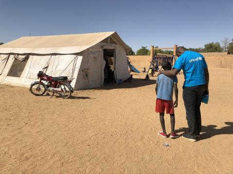 Seybou, a 12-year-old displaced boy from Mopti, talks to UNICEF Child Protection Specialist Boulkassoum Cissé in front of a Child-Friendly Space in Gao, northern Mali.