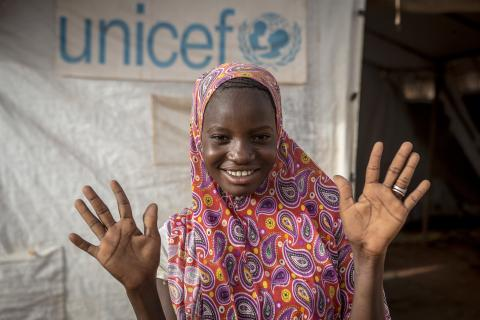 "Hawa Gadiaga, 15, who fled her village in 2019 following violence, shows off her clean hands at the Socoura displacement camp in Mopti, central Mali. Displacement sites, where families live in tents in close proximity and often have limited access to quality social services and information, are at high risk of becoming tinderboxes for the spread of COVID-19. As of 23 May 2020, Mopti region had recorded 72 cases of COVID-19. ""Hawa's especially committed to promoting key practices,"" says Oumar Gadiaga, a comm"