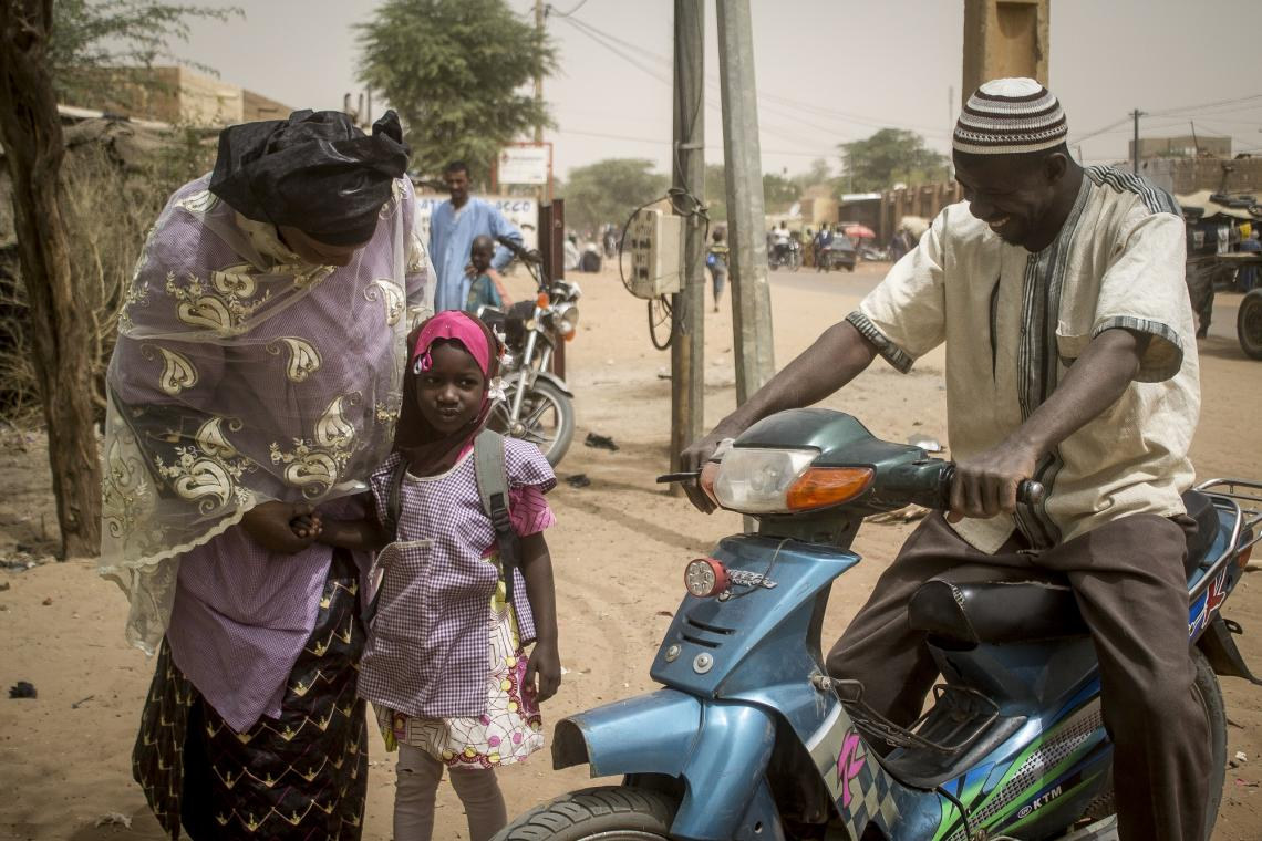 Mossa, 34, a security guard in Timbuktu, jumps on his motorcycle to bring his daughter Azahara Walett Mossa to a community pre-school located in the district of Djingareyber.