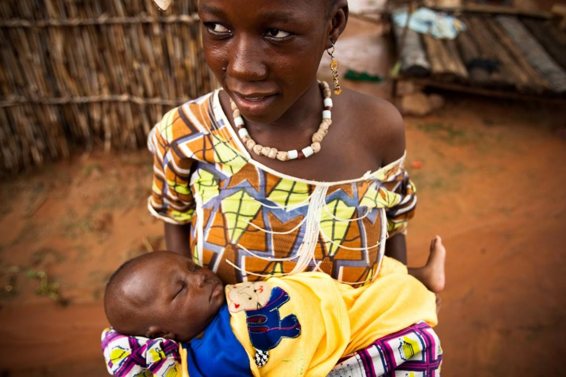 Arama Coulibaly, 15 years old, holds her 20-day-old baby.