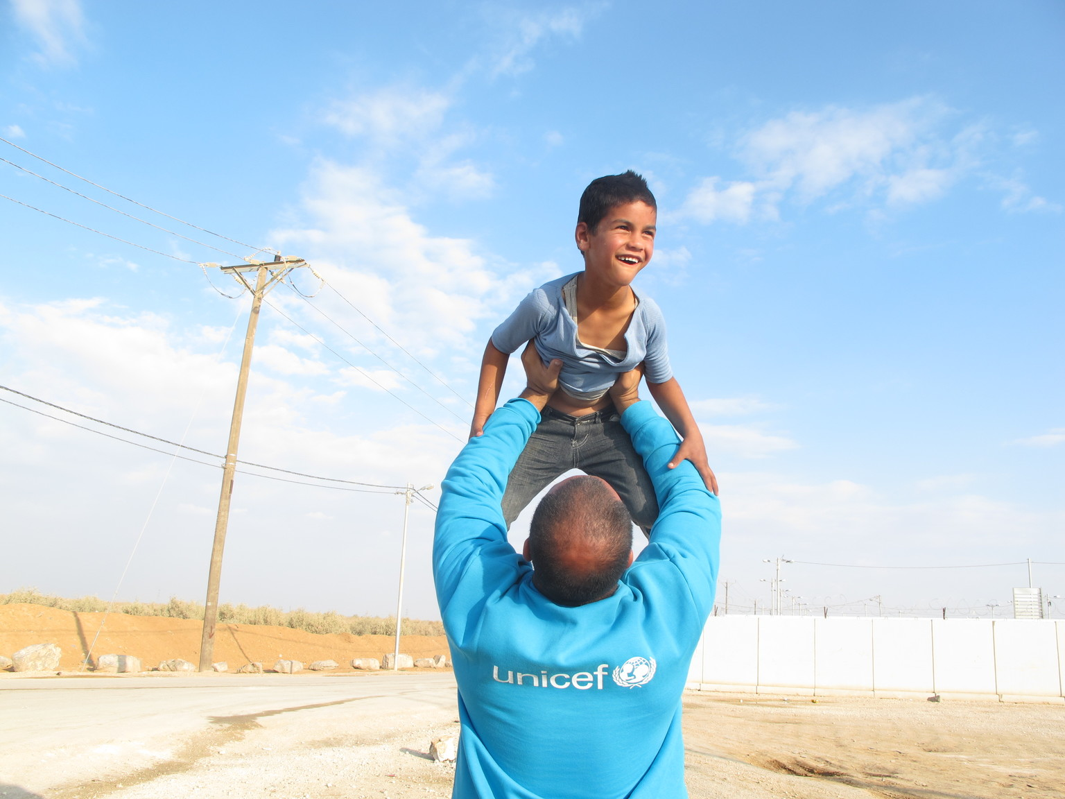 A UNICEF staff holding a child up