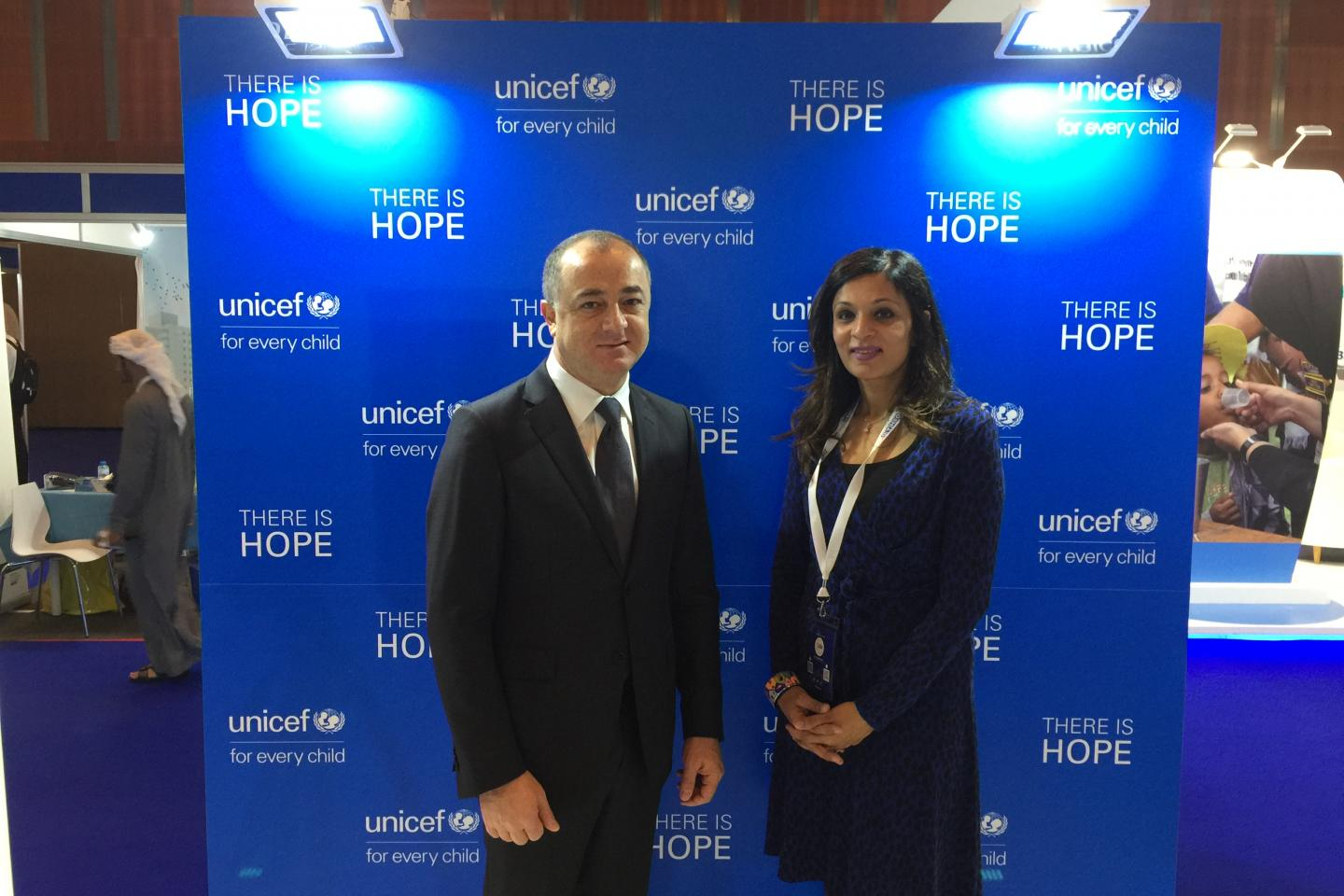 Two people taking a photo infront of a UNICEF banner