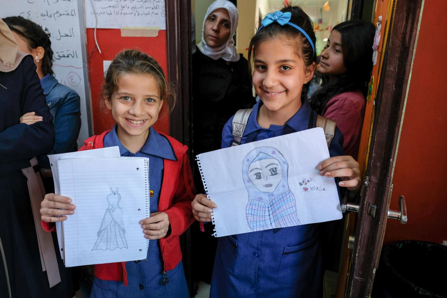 Two girls showing their drawings