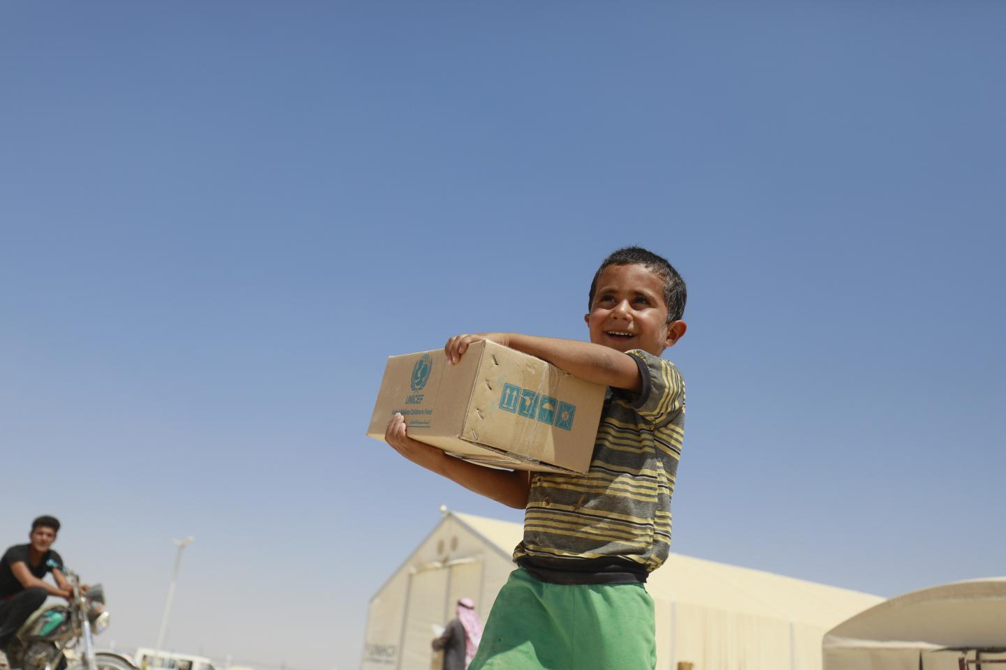 A child carrying a box