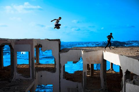 Children playing parkour in a destroyed building