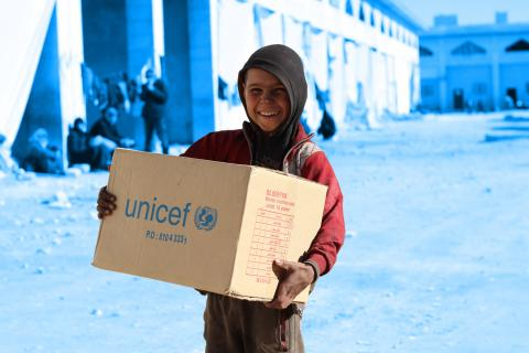 a boy holding a UNICEF branded box