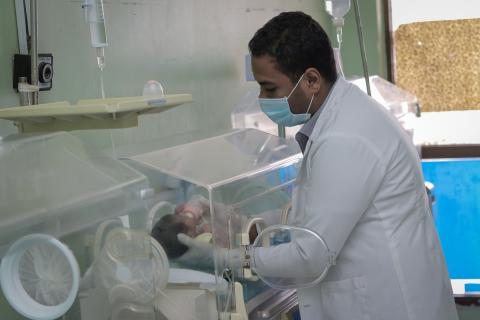a health worker taking care of a premature newborn