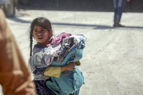 Young girl holding her belongings and walking
