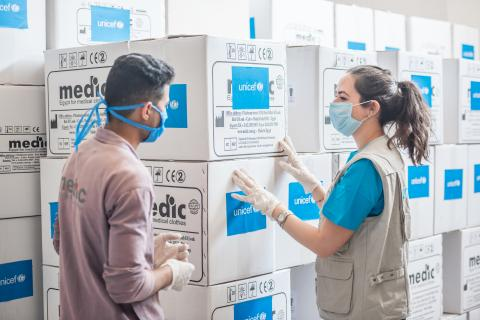 UNICEF staff talking to a warehouse worker in front of boxes of supplies