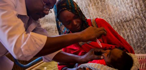 A worker vaccinate a child with oral drops while his mother is holding him