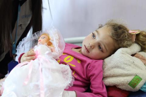 A girl in a hospital bed with her doll