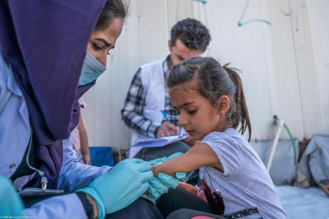 a health worker vaccinate a girl