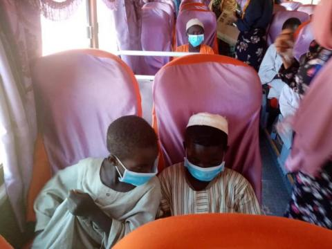 kids in a bus wearing face masks