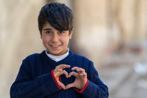 a boy making a heart gesture with his hands