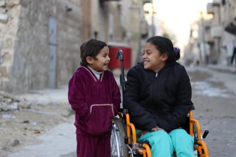 Two children in an alley. One of them is on a wheelchair
