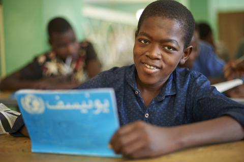 A boy smiles in a classroom as he write in a UNICEF branded notebook