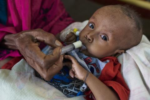an infant being fed by a syringe