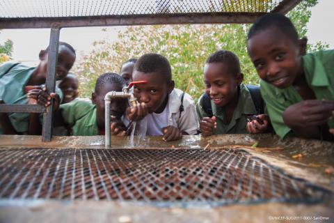 Kids gathered around and drinking water from a tab outdoors