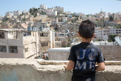 a boy looking over a town from a rooftop