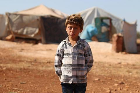 A boy standing in a camp