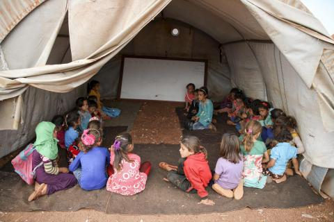 A group of kids attneding school in a tent