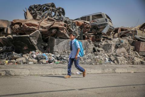 A school boy walking with his UNICEF backpack in front of rebel
