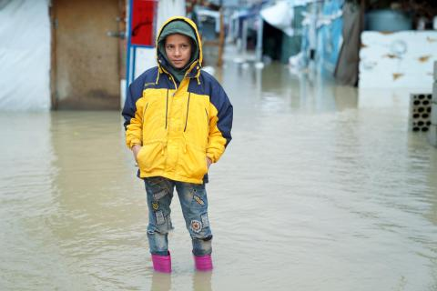a boy standing in water floods
