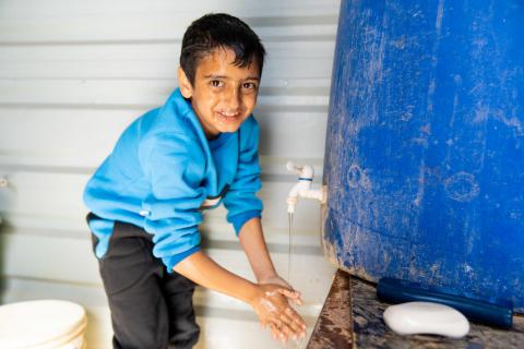 a boy washing his hands