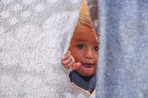 a boy peaking from behind a tent