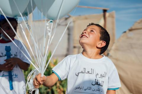 a boy holding Baloons
