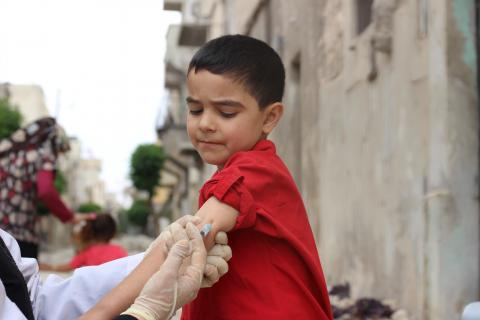 health worker vaccinates a boy using a syringe