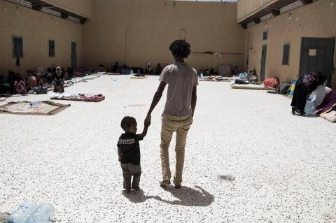 A father and a child in a detention facility