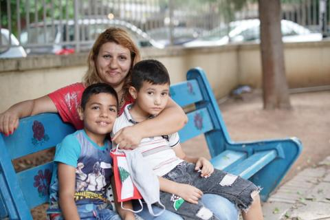 a mother and two boys sitting on a bench