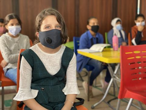 a girl wearing mask in a classroom