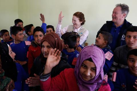 UNICEF Executive Director in the middle of kids, high-fiving a child