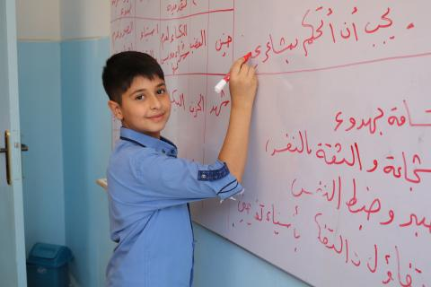 a boy writing on the board in a classroom