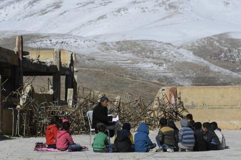 a group of kids with a teacher in a cirlcle outdoors