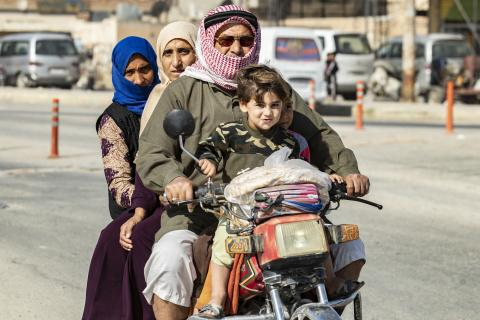 a family riding a motorcycle as they flee violence